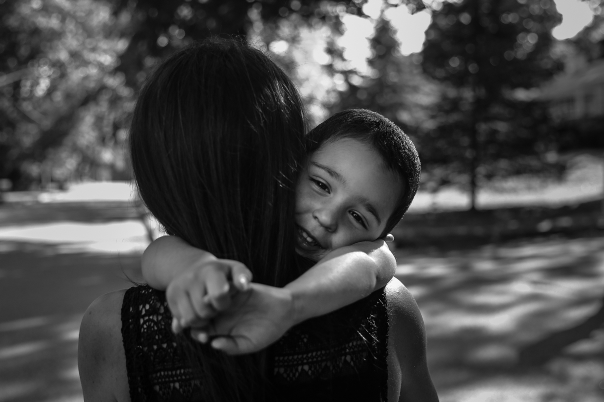 Boy smiles while being held by mother