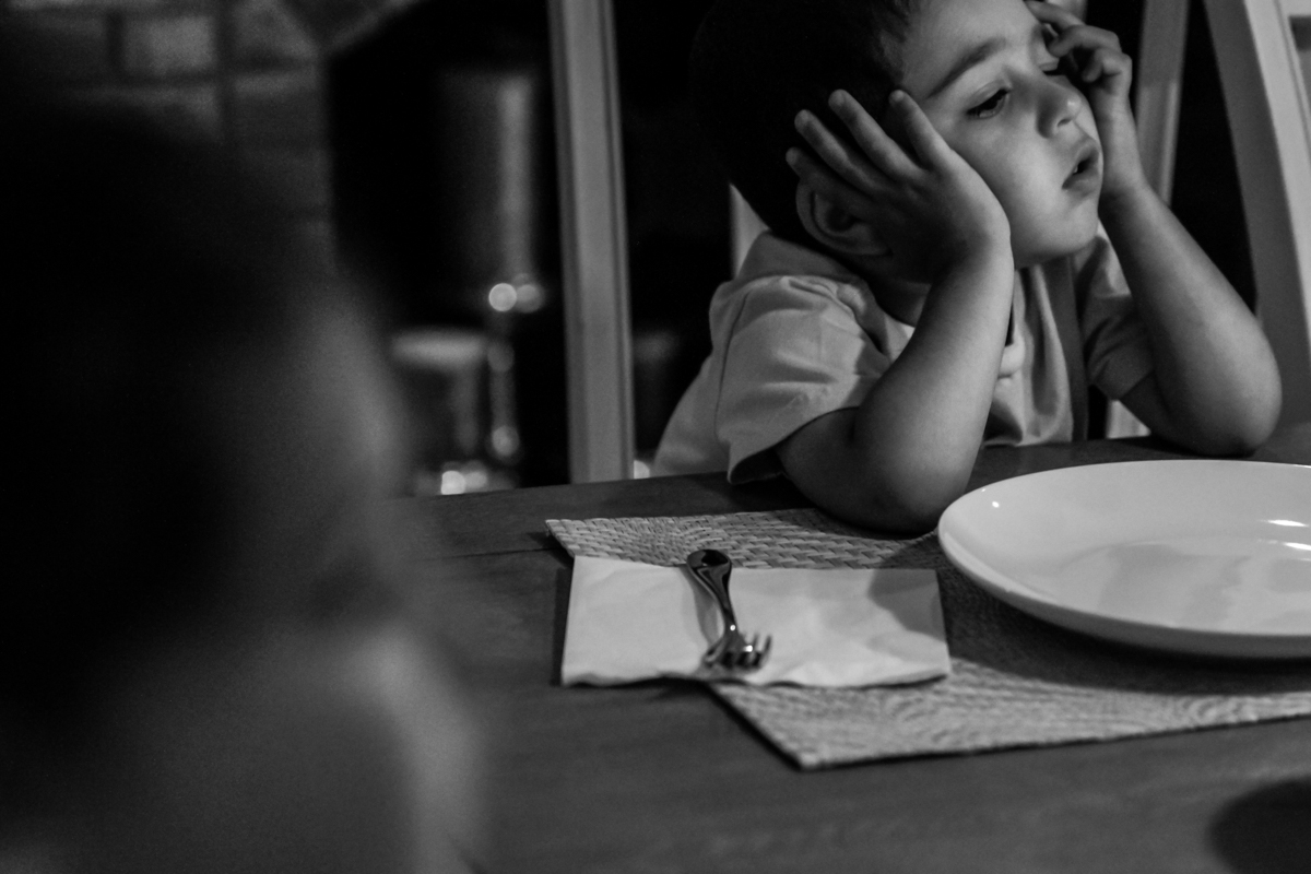 Tired boy rests head on hands at dining table