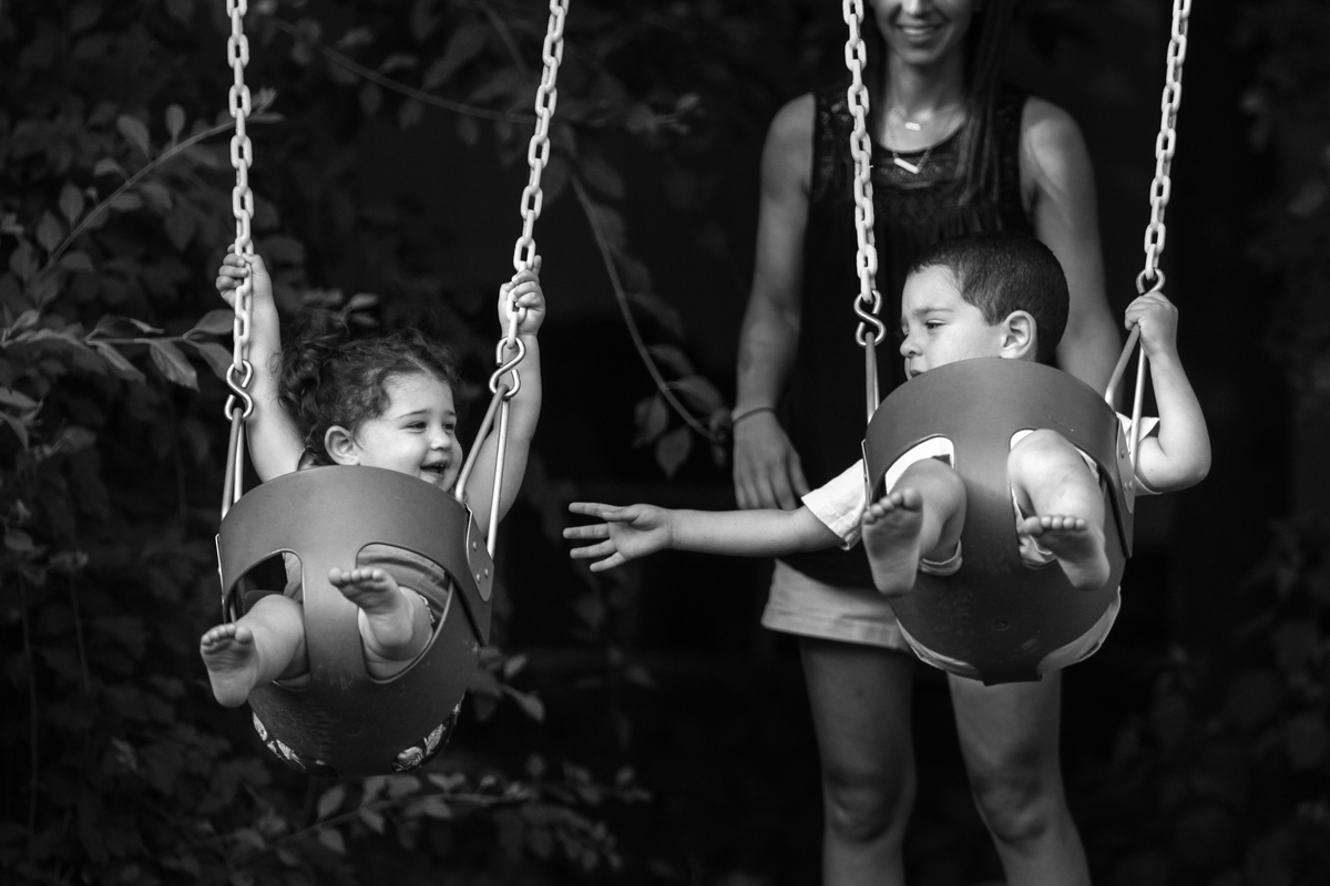 Boy seated in swing reaches out to girl seated in swing