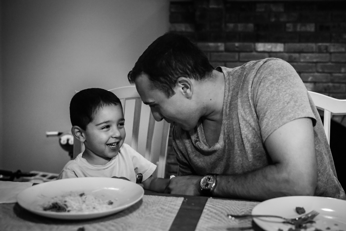 Father and soon smile at each other at dinner table