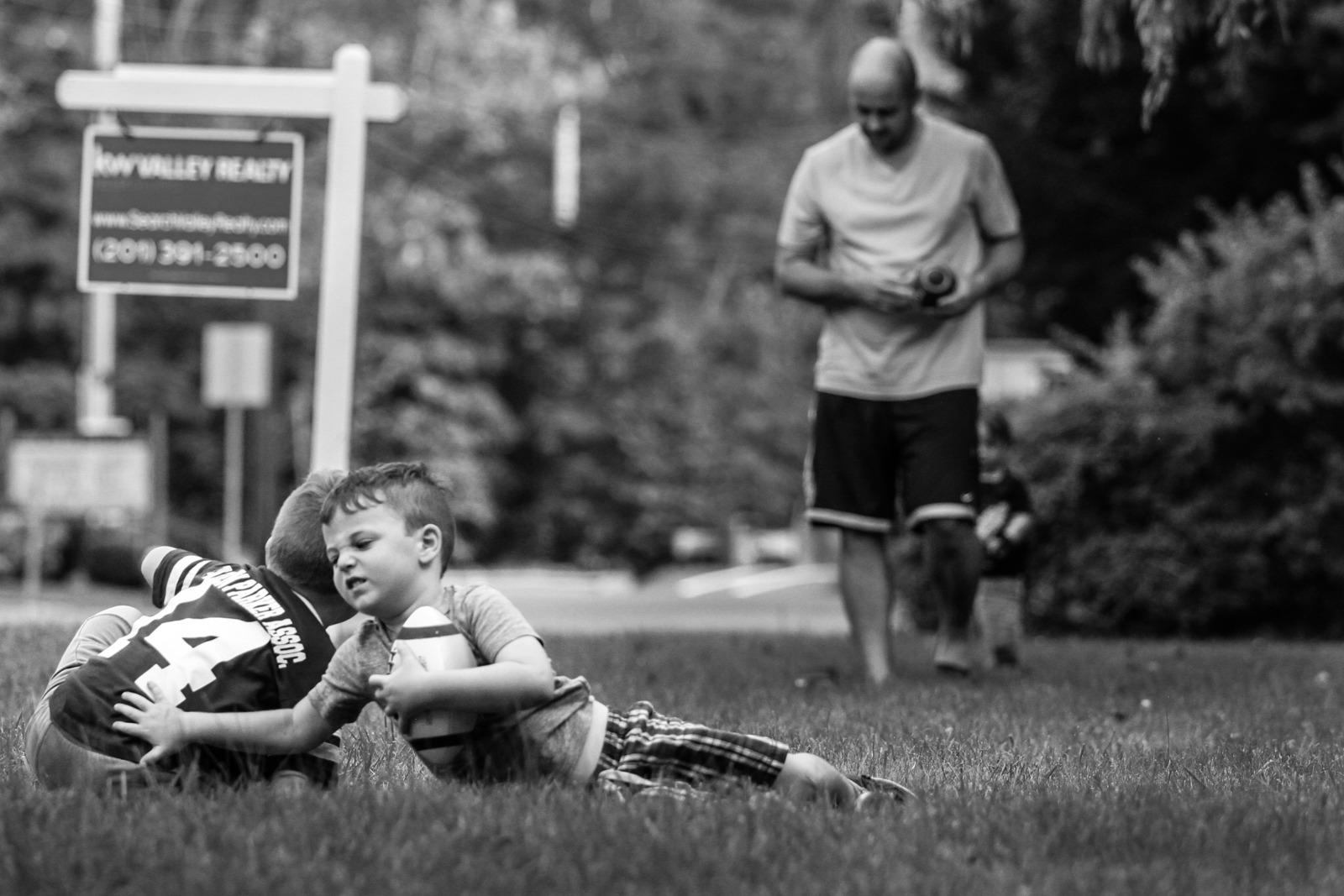 Two boys wrestle on the grass with football