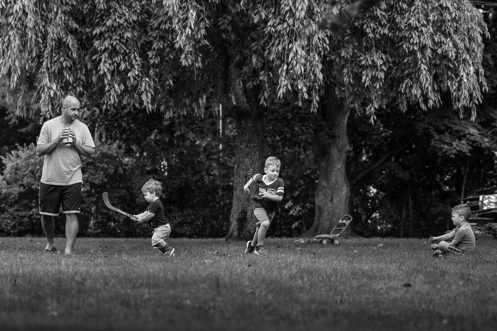 Man gets ready to throw football to his three sons