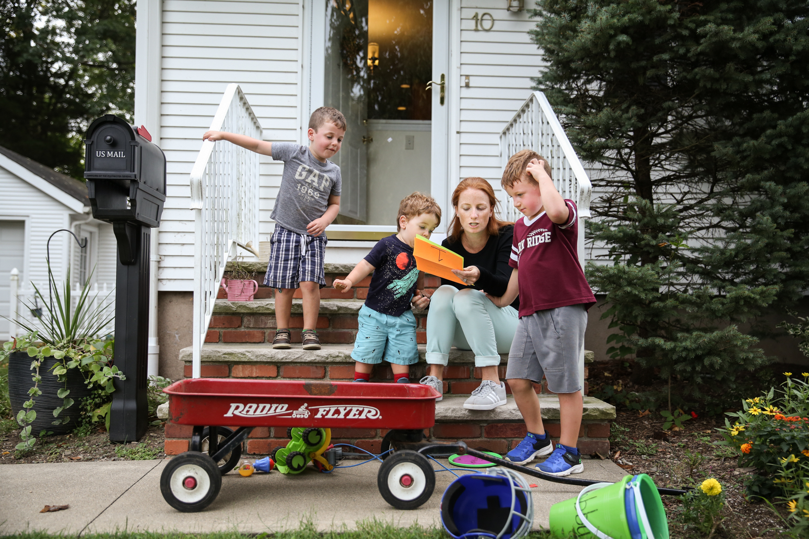 Woman reads paper to her three sons while sitting on front step