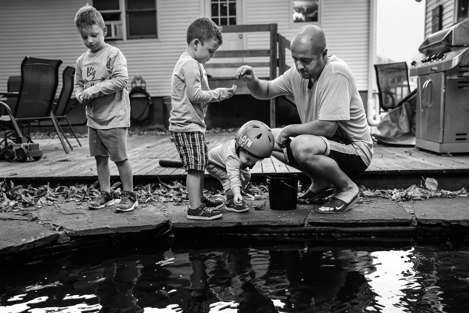 Man hands out fish food to three boys standing next to coy pond