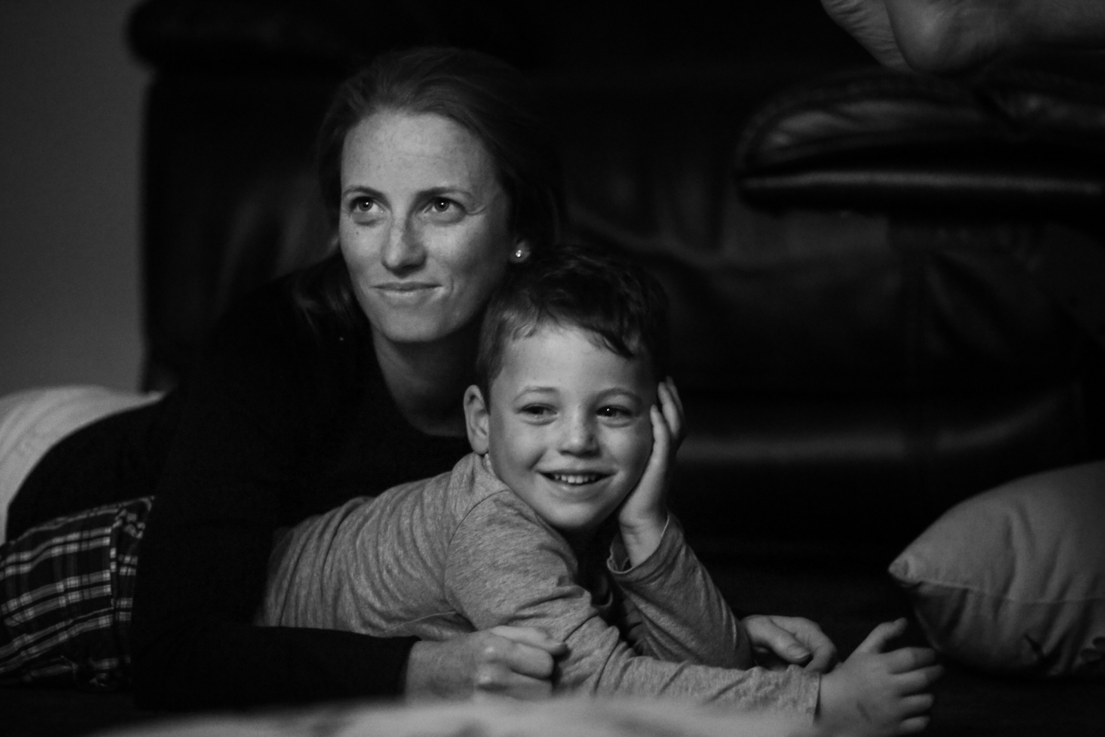 Woman leans over smiling boy with hand by his face