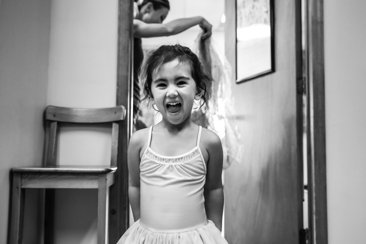 Girl smiles while stepping through doorway with teacher holding scarves