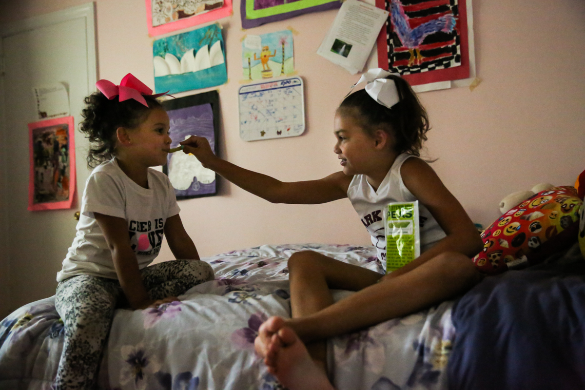 Girl feeds sister a snack while sitting on bed