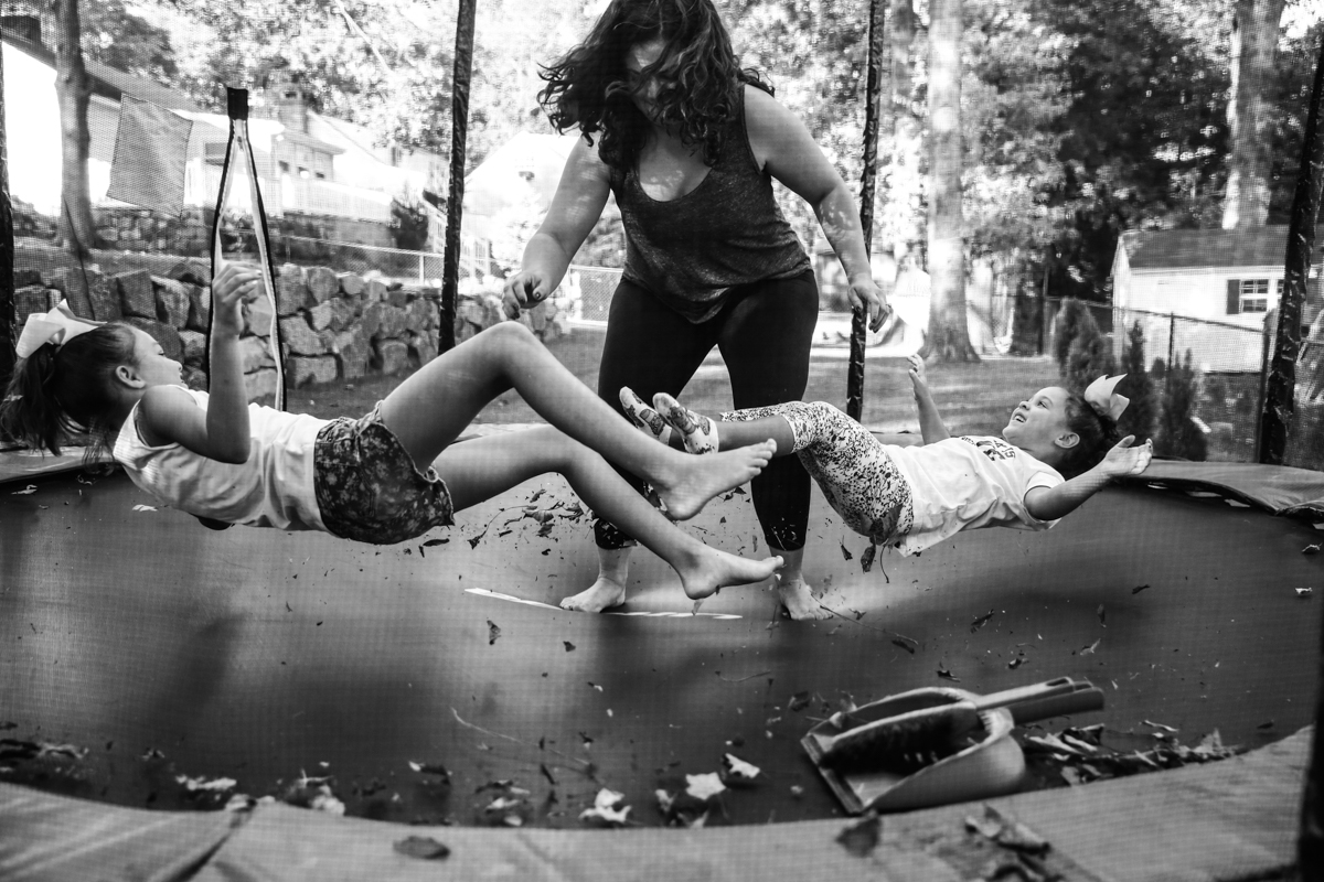 Woman jumps on trampoline making two girls lying down jump up