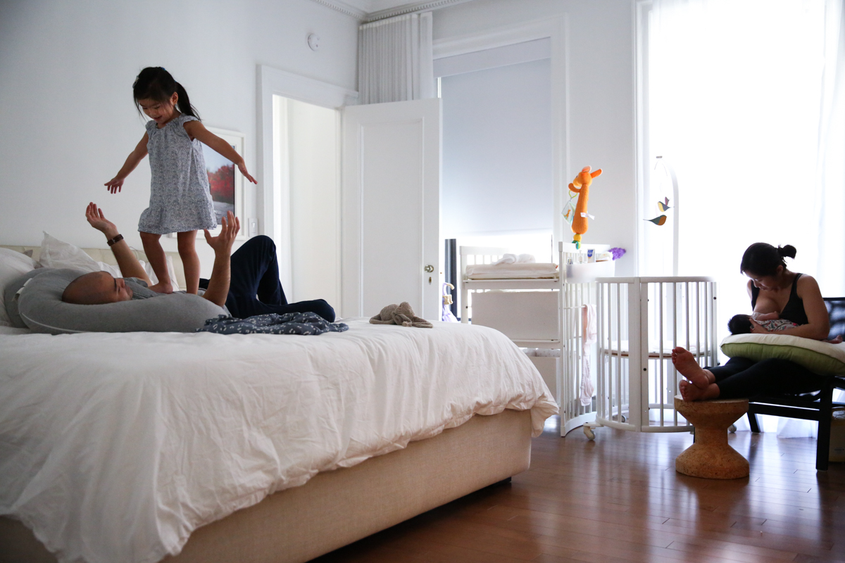 Child stands on man lying on bed while woman nurses baby in chair
