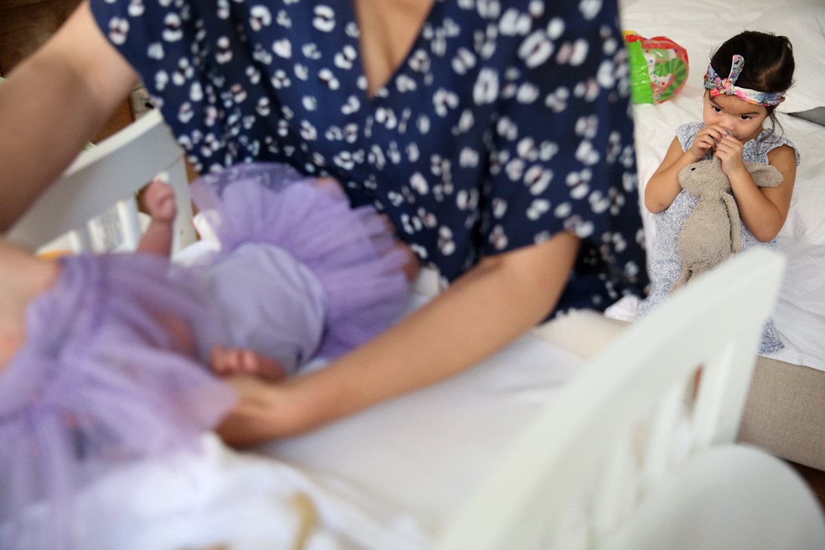 Child holds stuffed bunny while watching mother dress baby