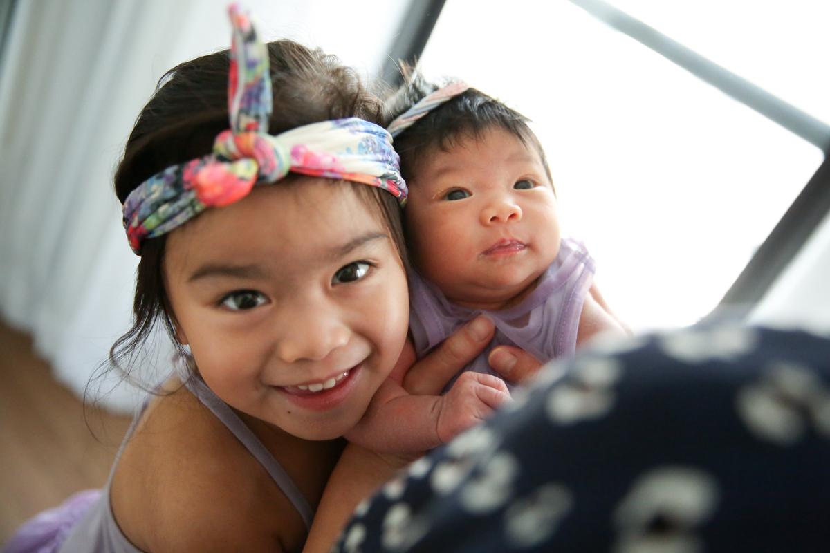 Girl smiles next to baby sisterM