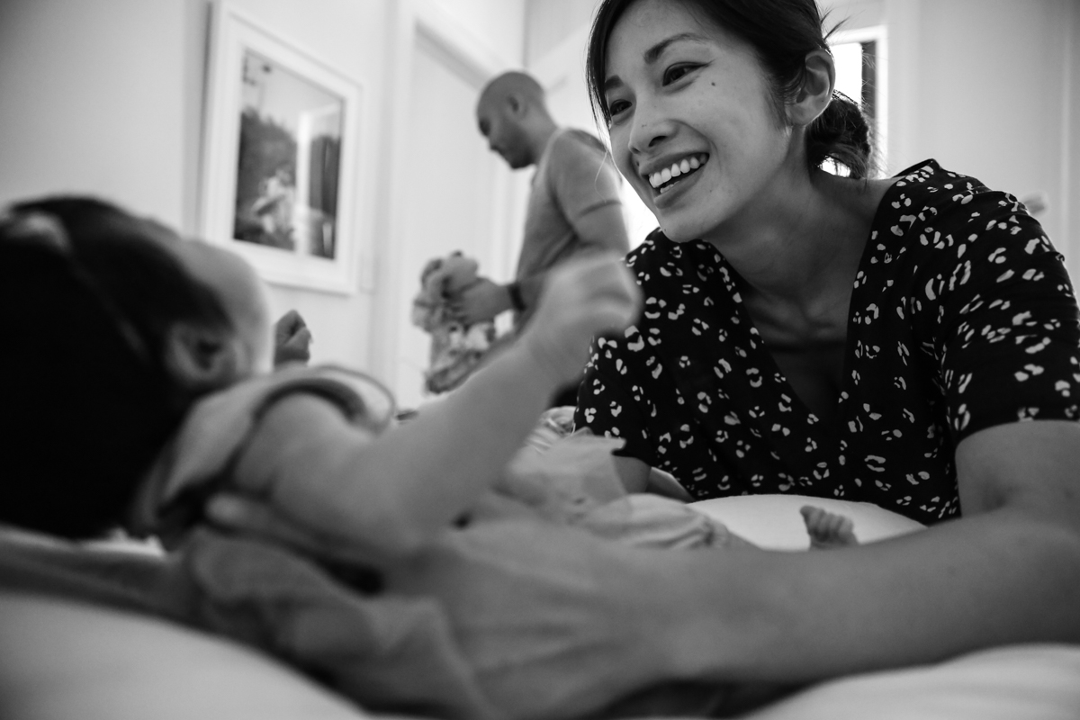 Woman smiles while picking up baby