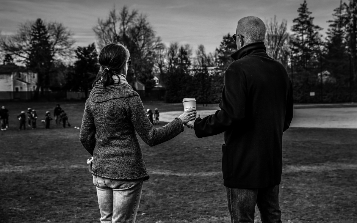 Woman and man hold a disposable coffee cup while looking out at a playing field