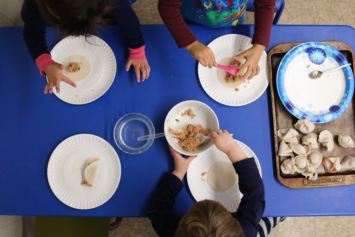 View from above of children working together to wrap dumplings