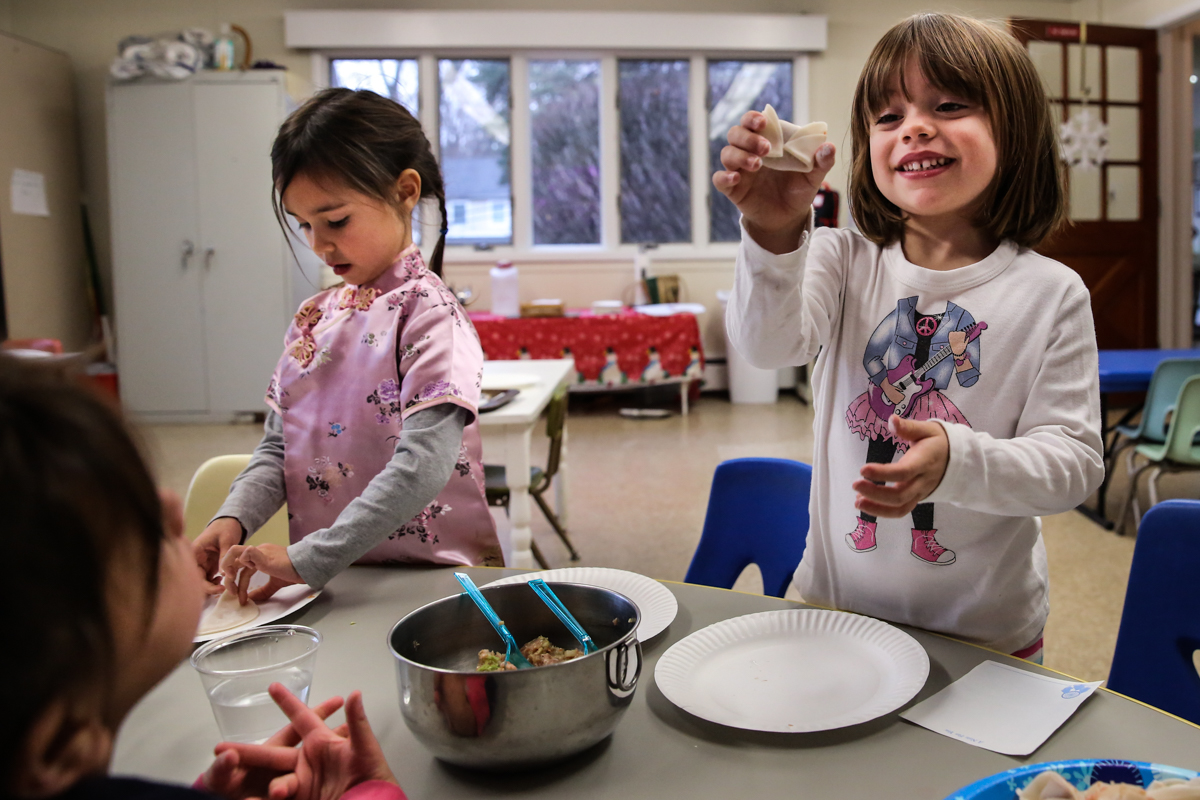 Girl proudly holds up wrapped dumpling in classroom setting