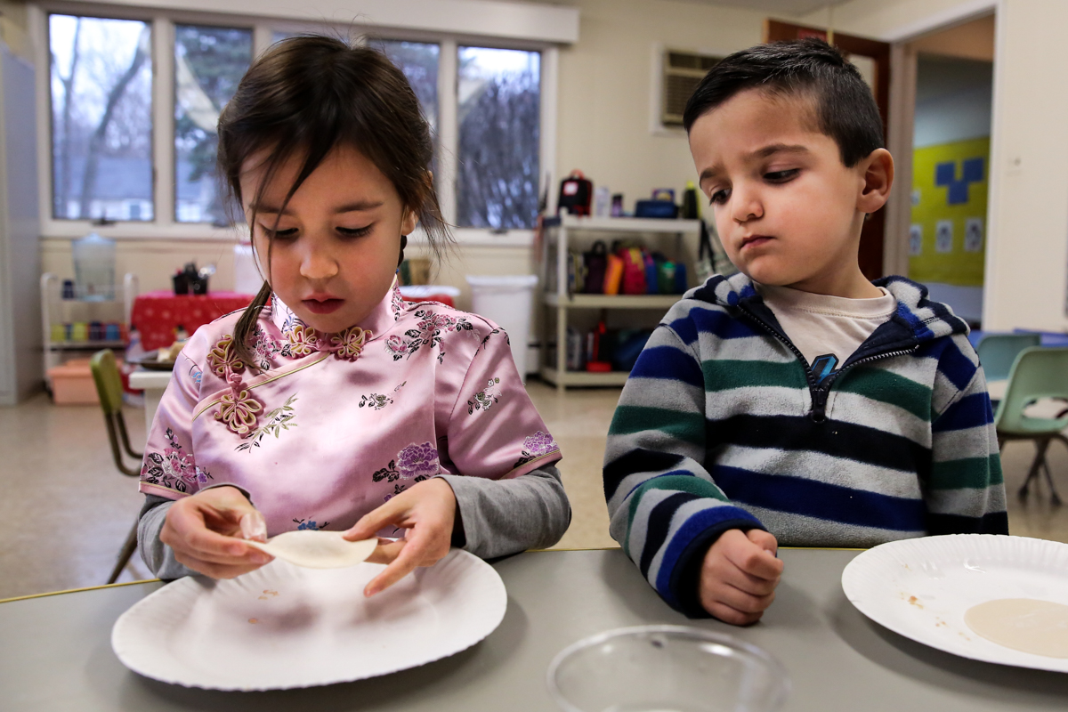 Girl wraps dumpling on a plate while boy looks over skeptically