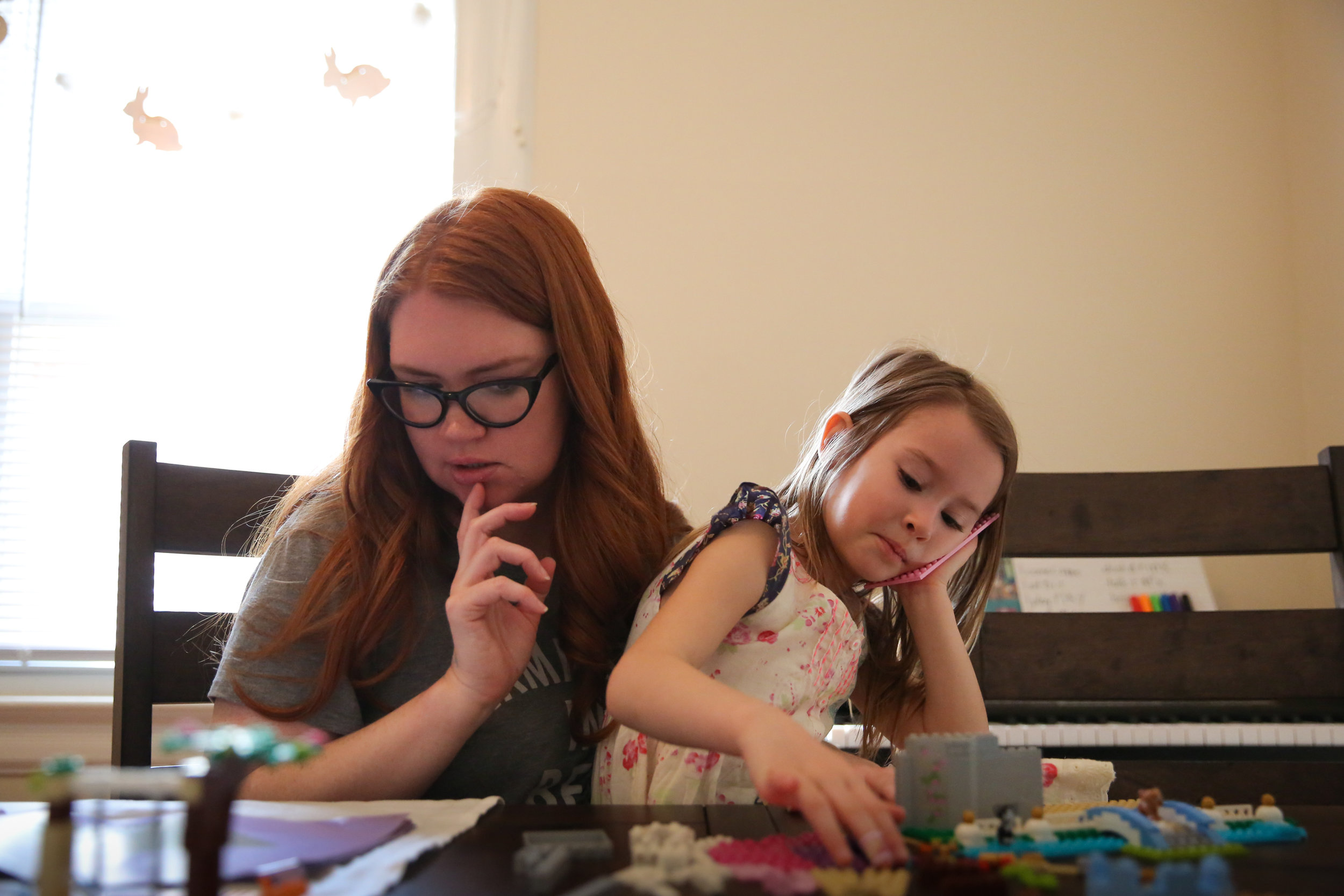 Woman and girl sit at table to build Legos