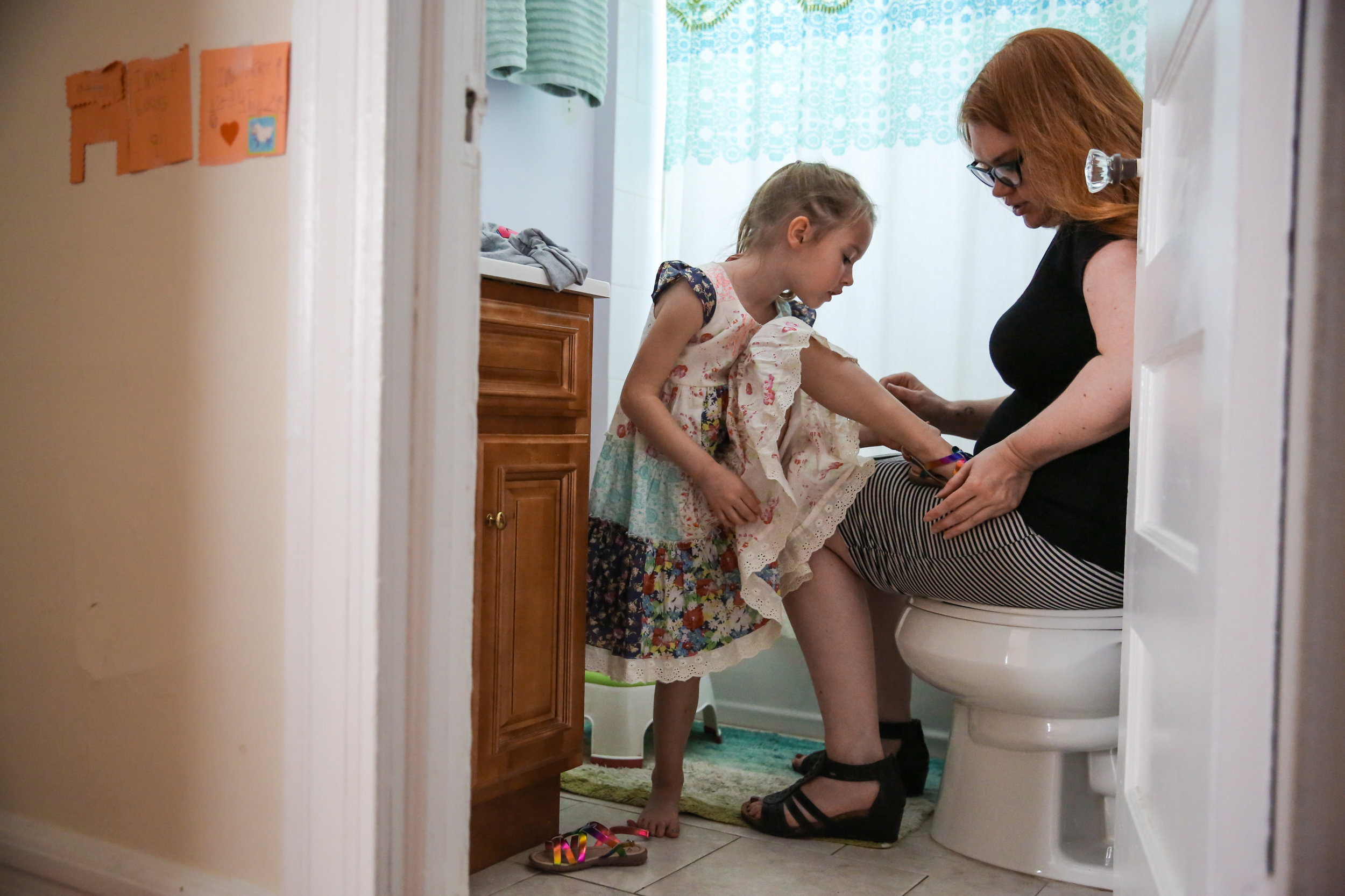 Woman checks girl's leg while sitting in bathroom