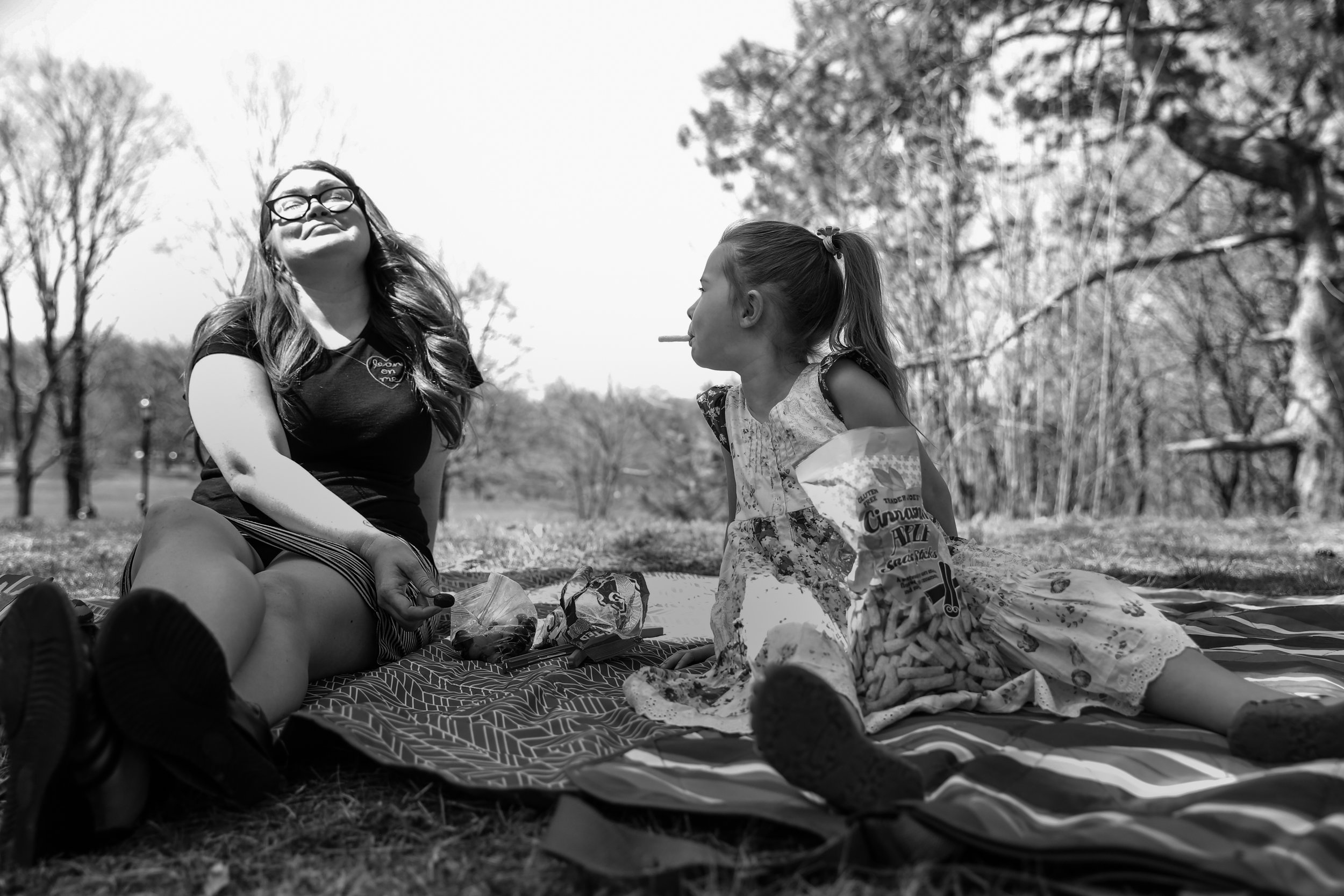 Girl sticks snack out of her mouth while sitting on picnic blanket with seated woman