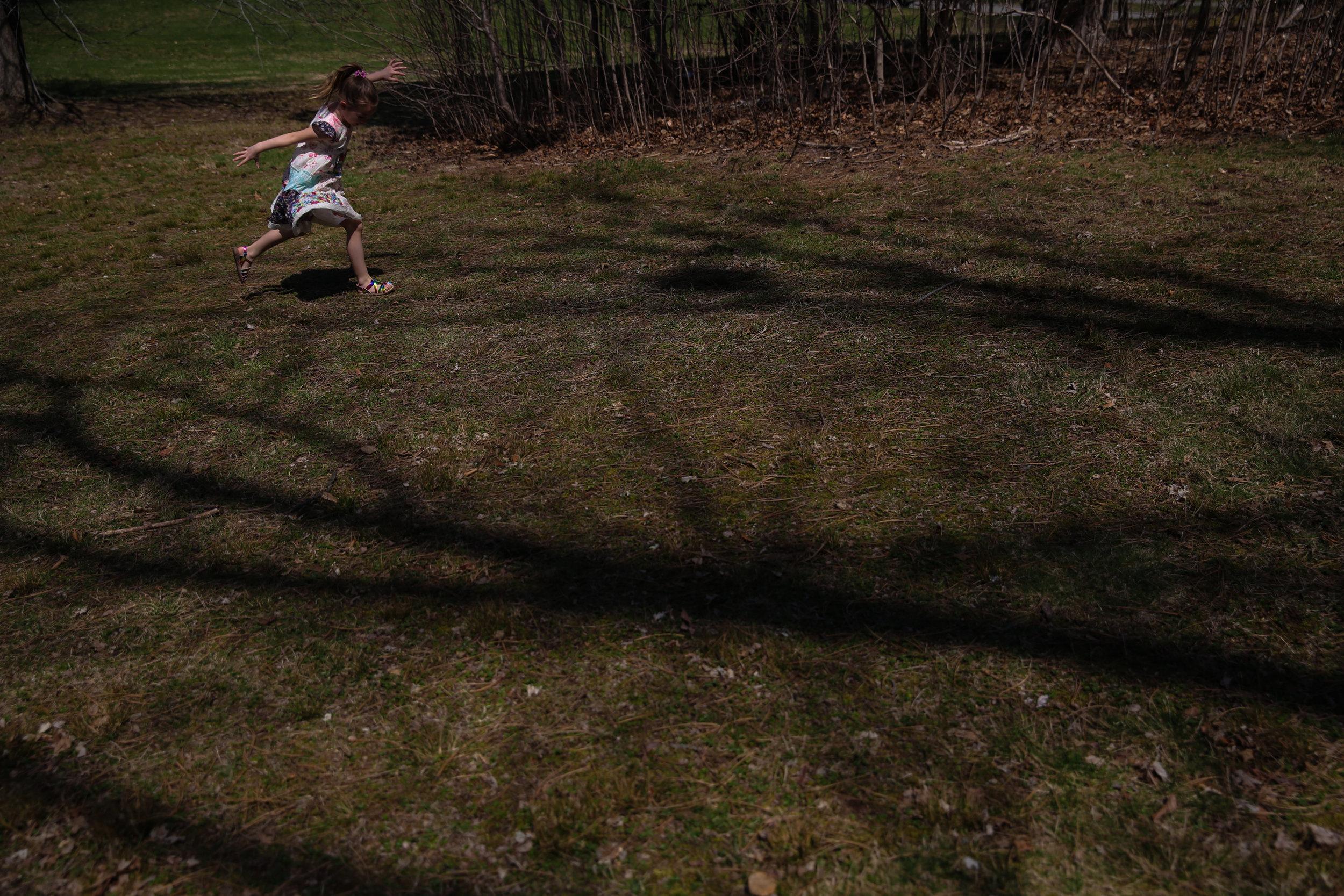 Girl frolics through tree shadowed lawn