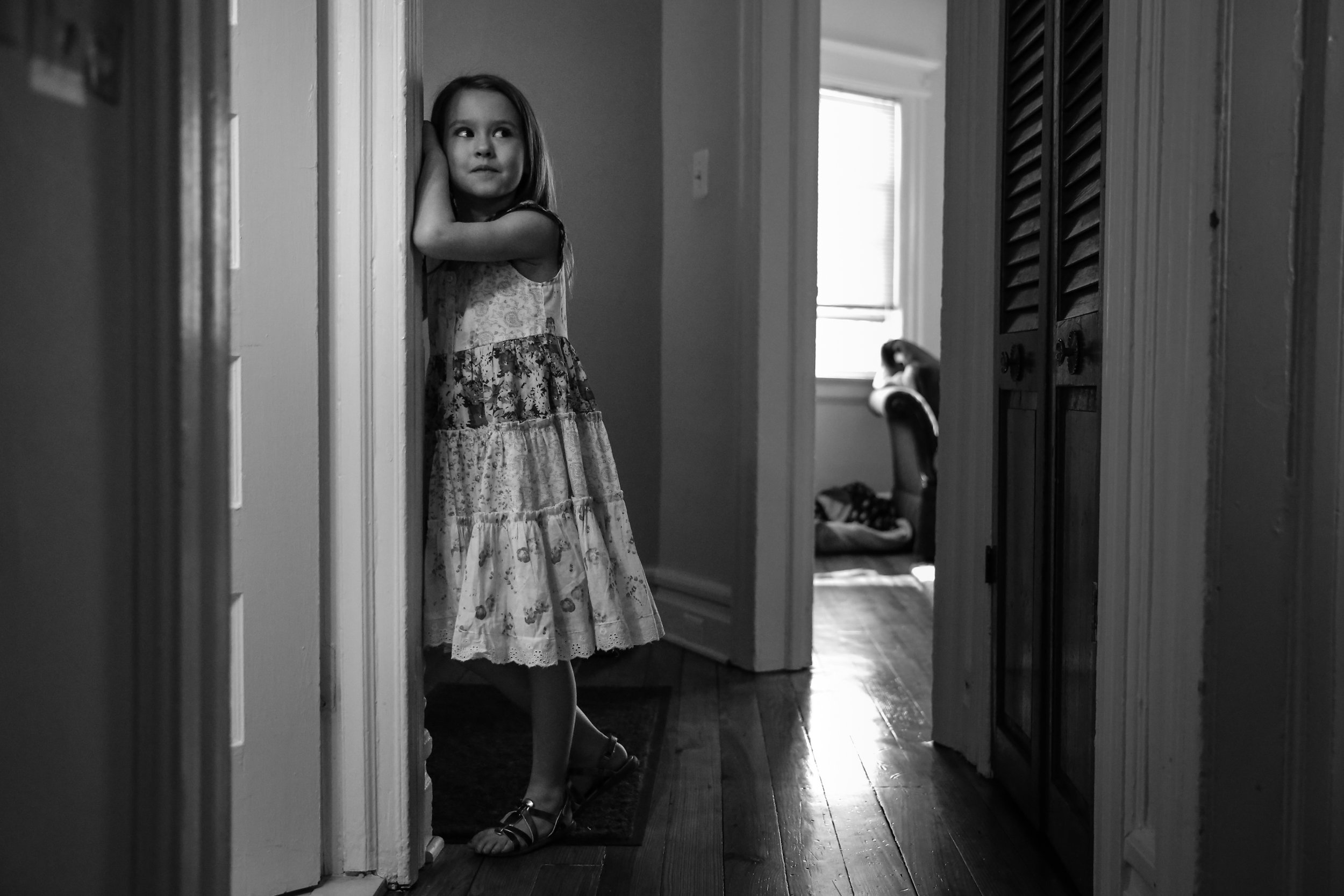 Girl stands and leans against hallway wall