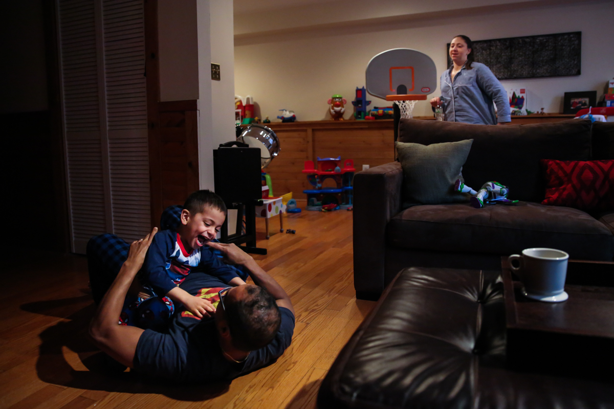 Boy and father wrestle on floor while woman walks behind couch