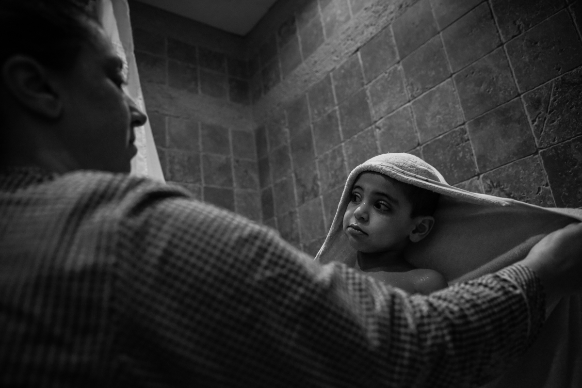 Boy wrapped in towel looks up at mother while standing in tub