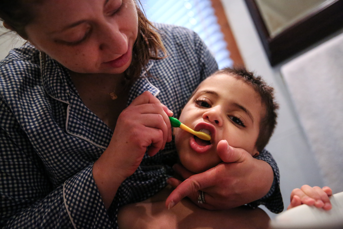 Woman brushes boys teeth