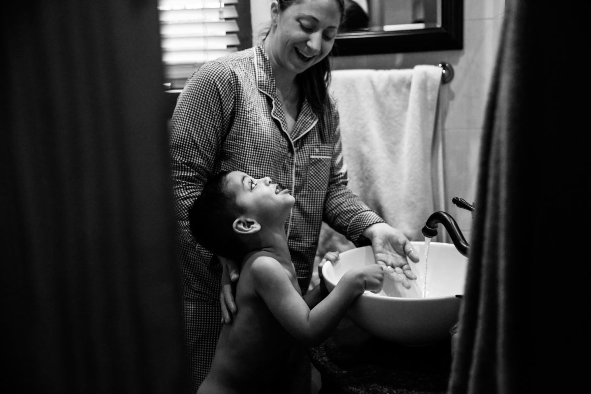 Boy and woman share a smile at bathroom sink