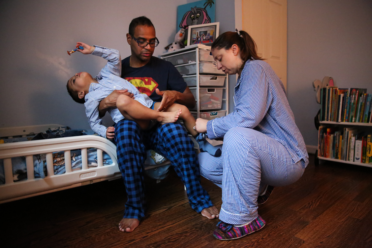 Boy plays with figurine while mom and dad try to put socks on boy