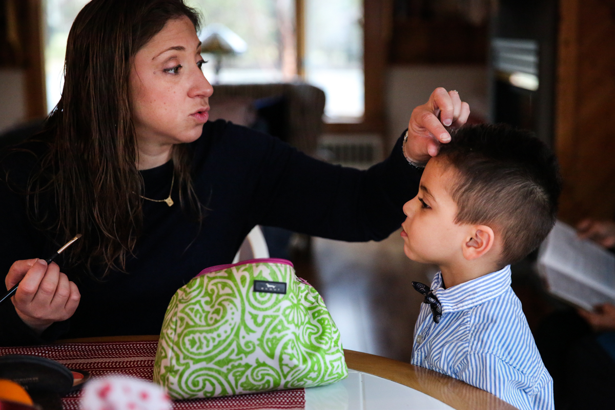 Woman fixes boy's hair while doing her makeup