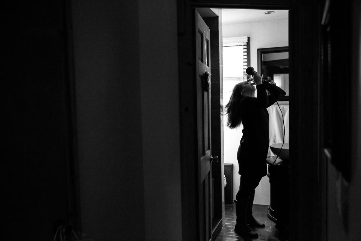 Woman blowdries her hair while standing in bathroom doorway