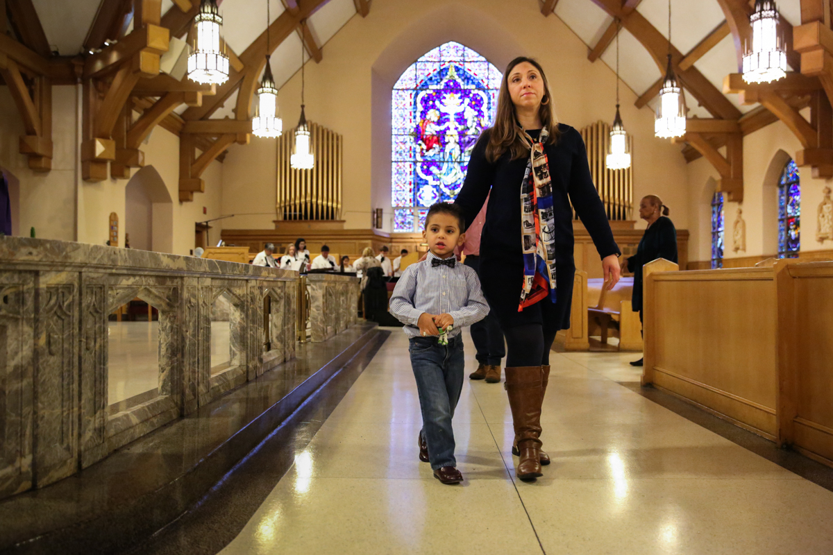Woman and boy walk down aisle in church