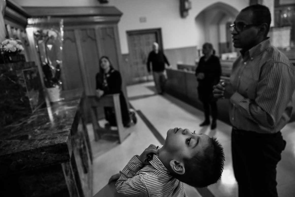 Boy grabs his collar while family members pray