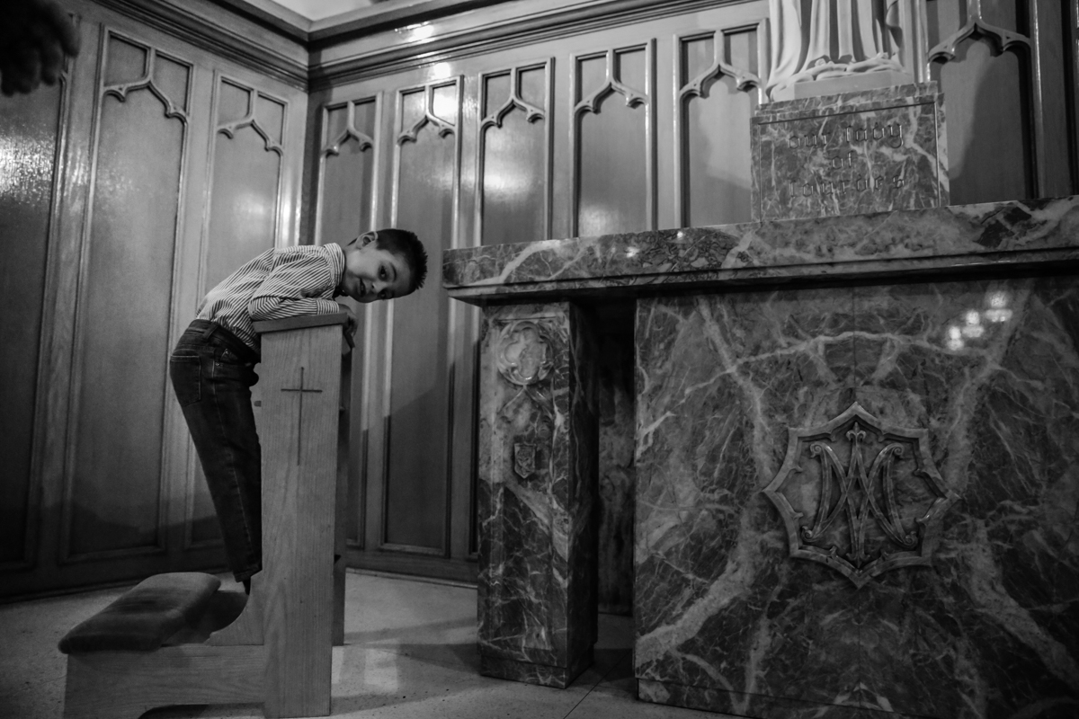 Boy leans over pew at base of statue