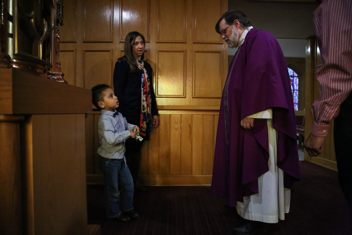 Priest dressed in mass robes greets boy and woman