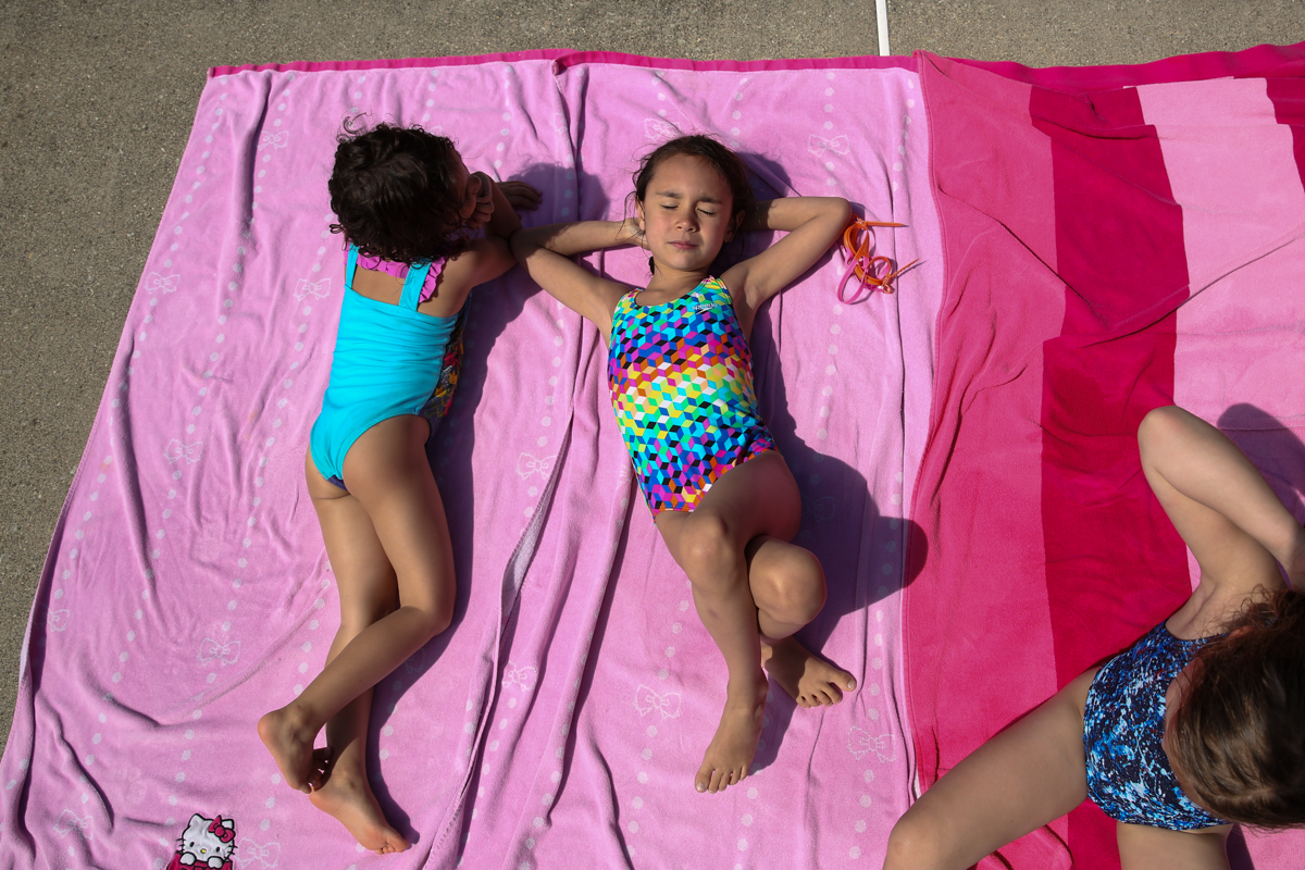 Girls sunbathe on pink towels