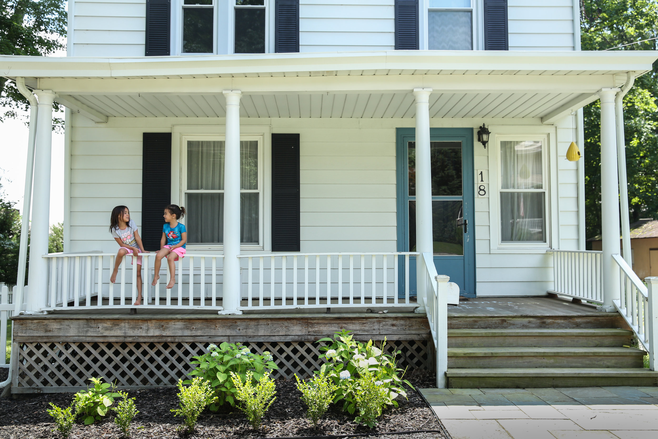 Two girls sit on railing of front porch