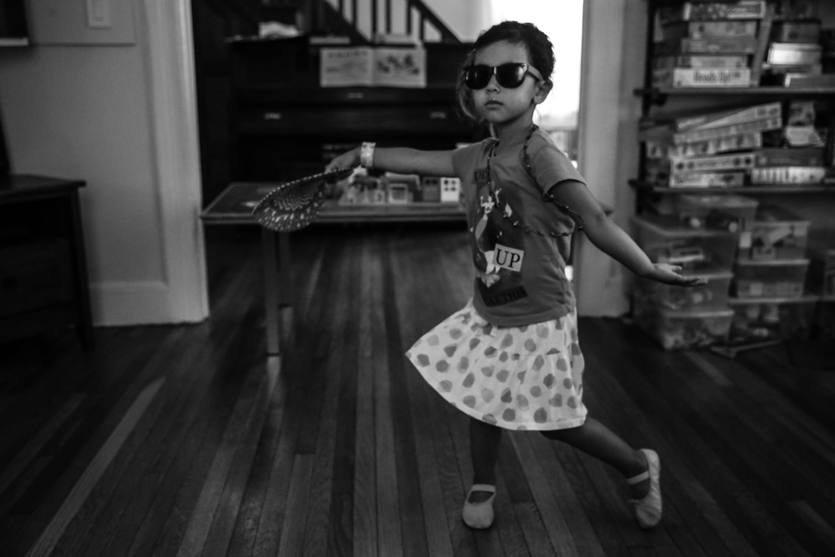 Girl with sunglasses dances in livingroom