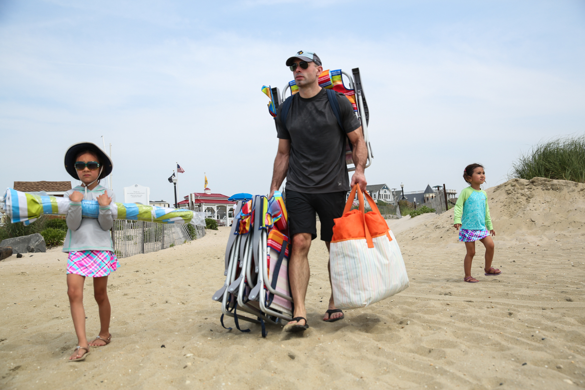 Man walks with 2 children while carrying beach chairs and beach bag onto the sandy beach. Girl with hat and sunglasses carries beach umbrella