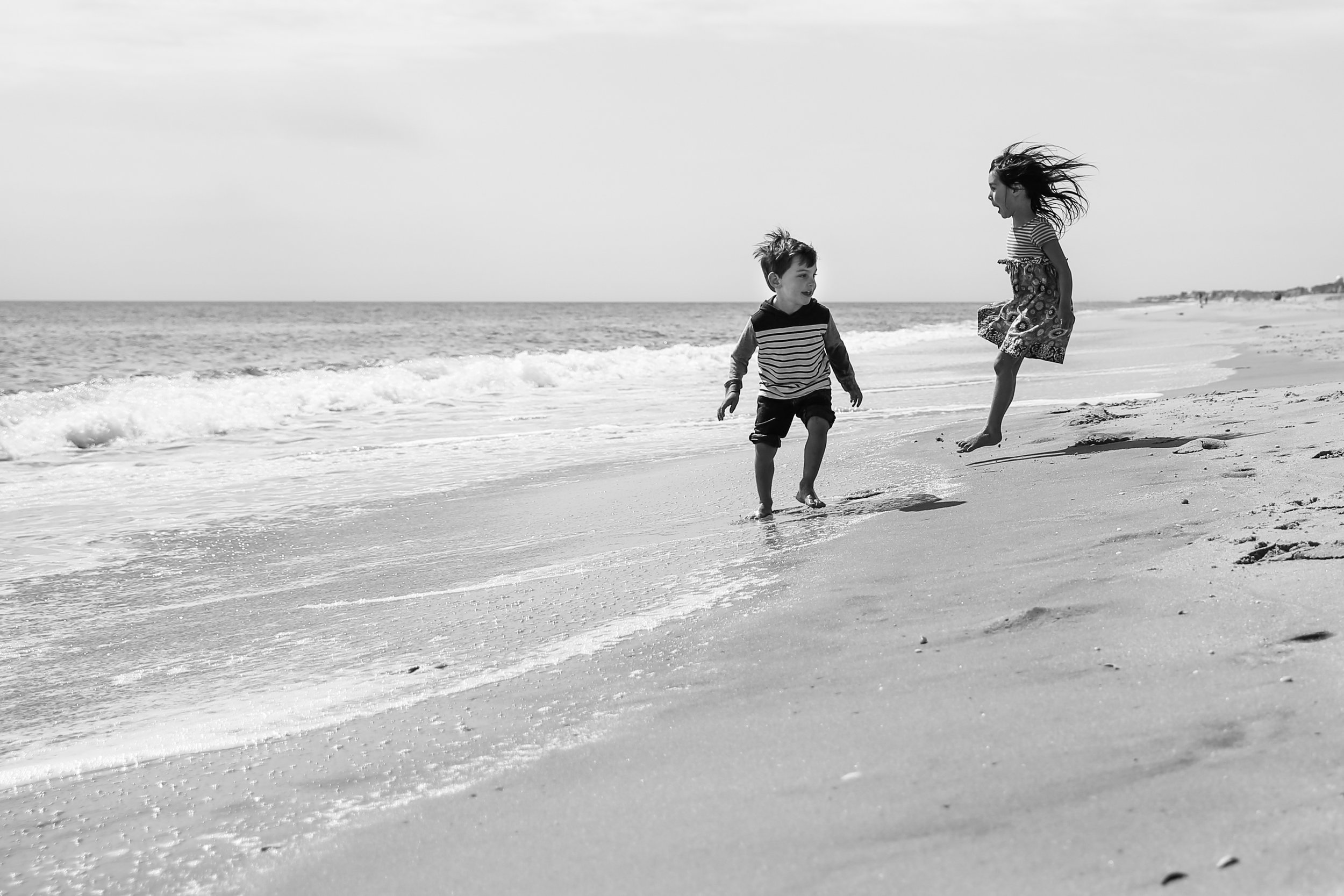 Boy and girl play and jump on the beach as ocean waves roll in