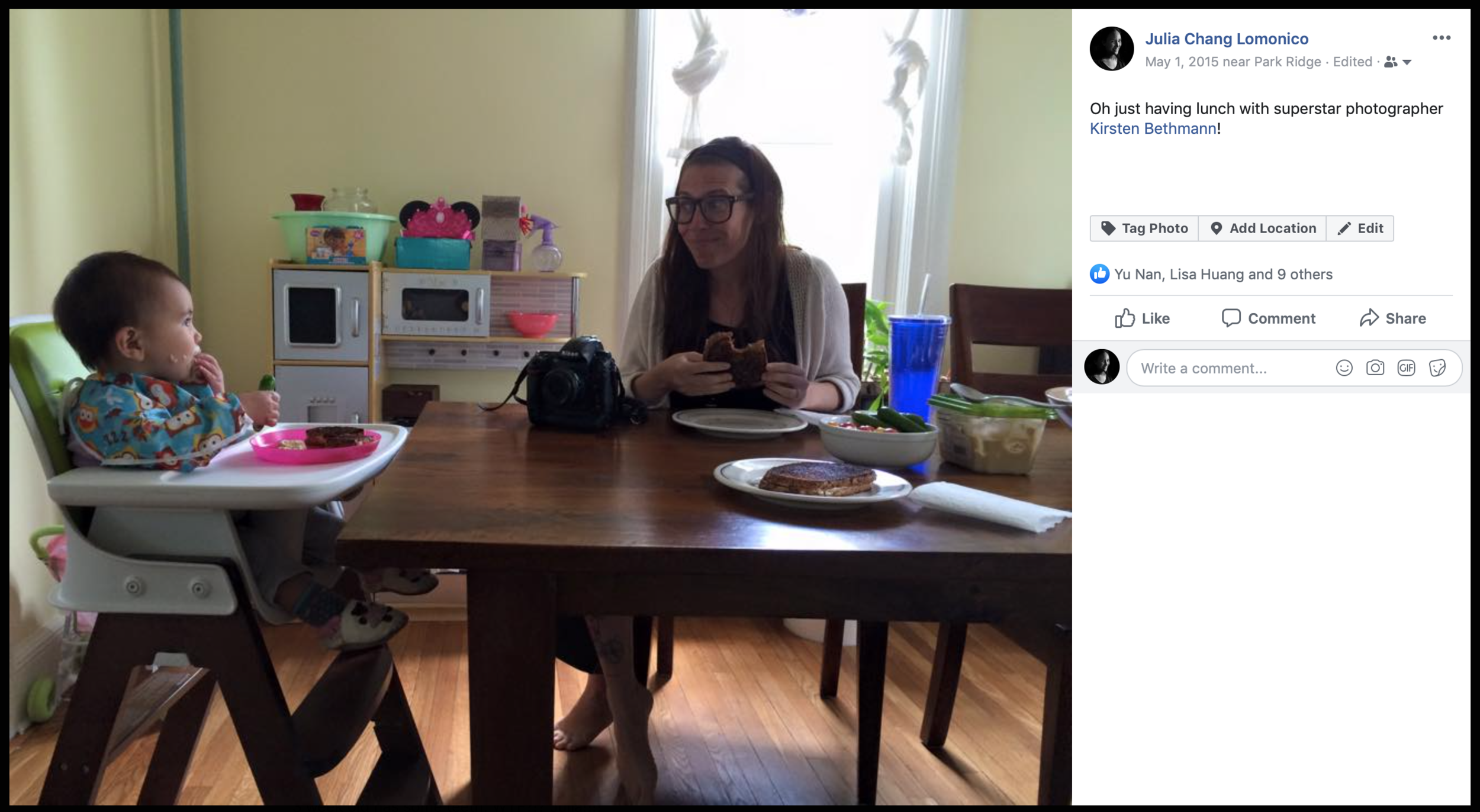 Woman with glasses eats sandwich at table while baby in high chair eats off a pink plate