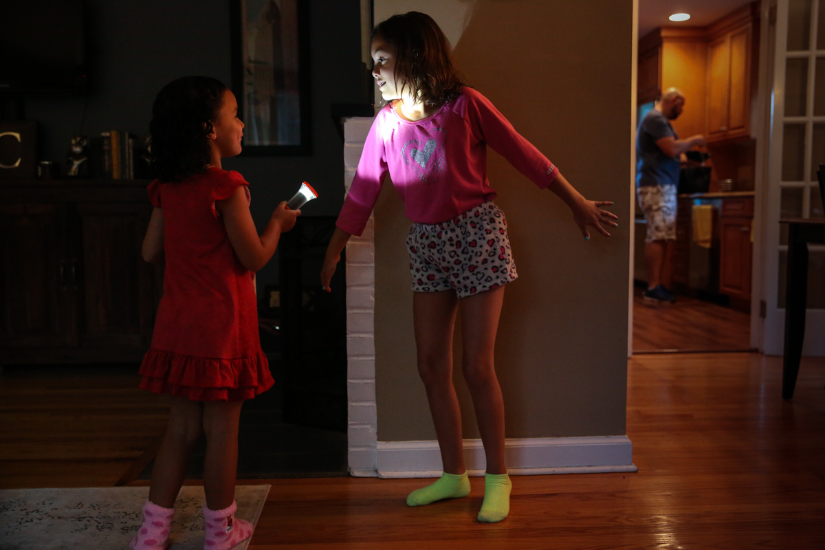 Girl holds flashlight and shines in other girls face while standing against a wall
