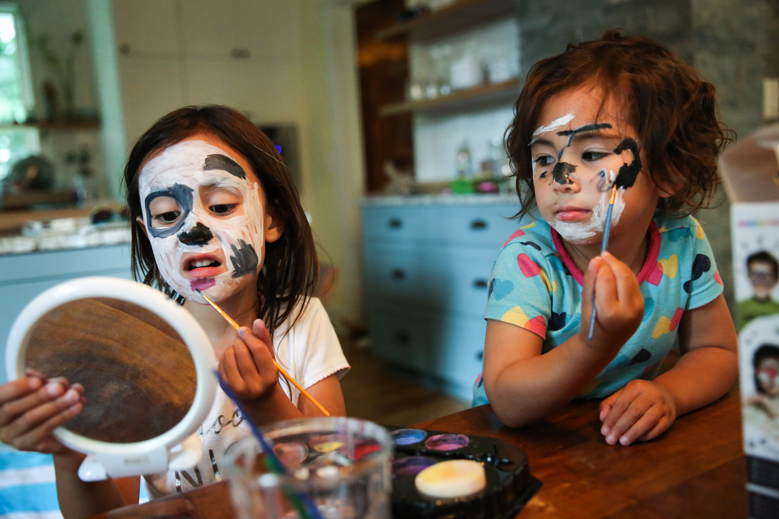 Two kids painting faces at table