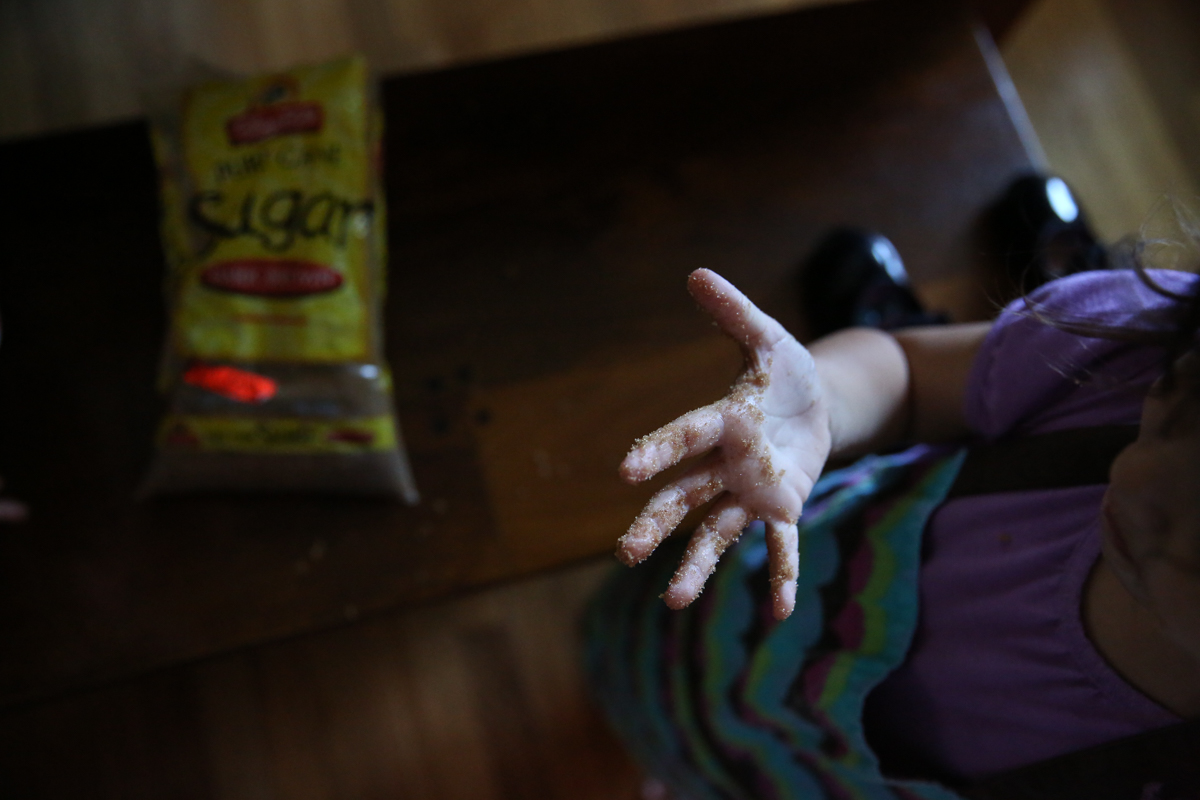 Child's hand covered in brown sugar