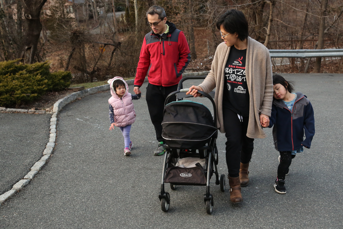 Man, woman and two children walk on street while woman pushes snap n go stroller. Girl holds woman's hand while eyes closed