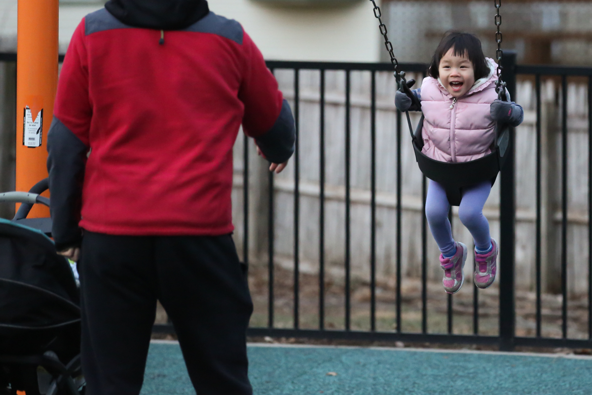 Man in red sweatshirt pushes girl wearing pink vest on swing