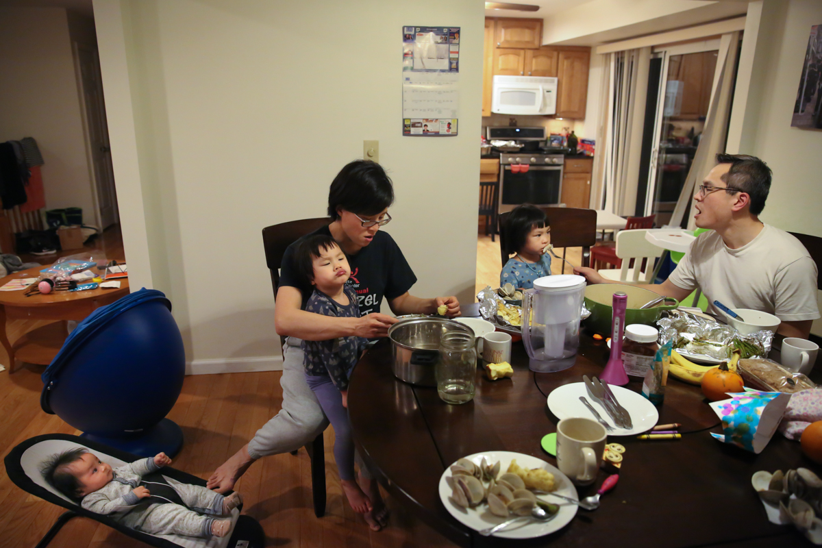 Family sits at dinner table—parents try to feed two girls while baby sits in bouncer on floor with mother pushing with her foot