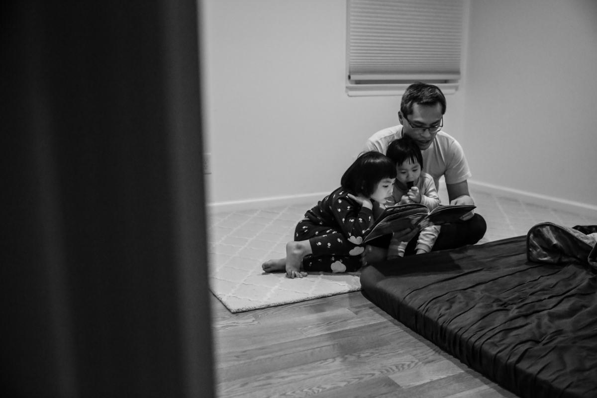 Man with glasses sits on rug with two children in pajamas, reading a book