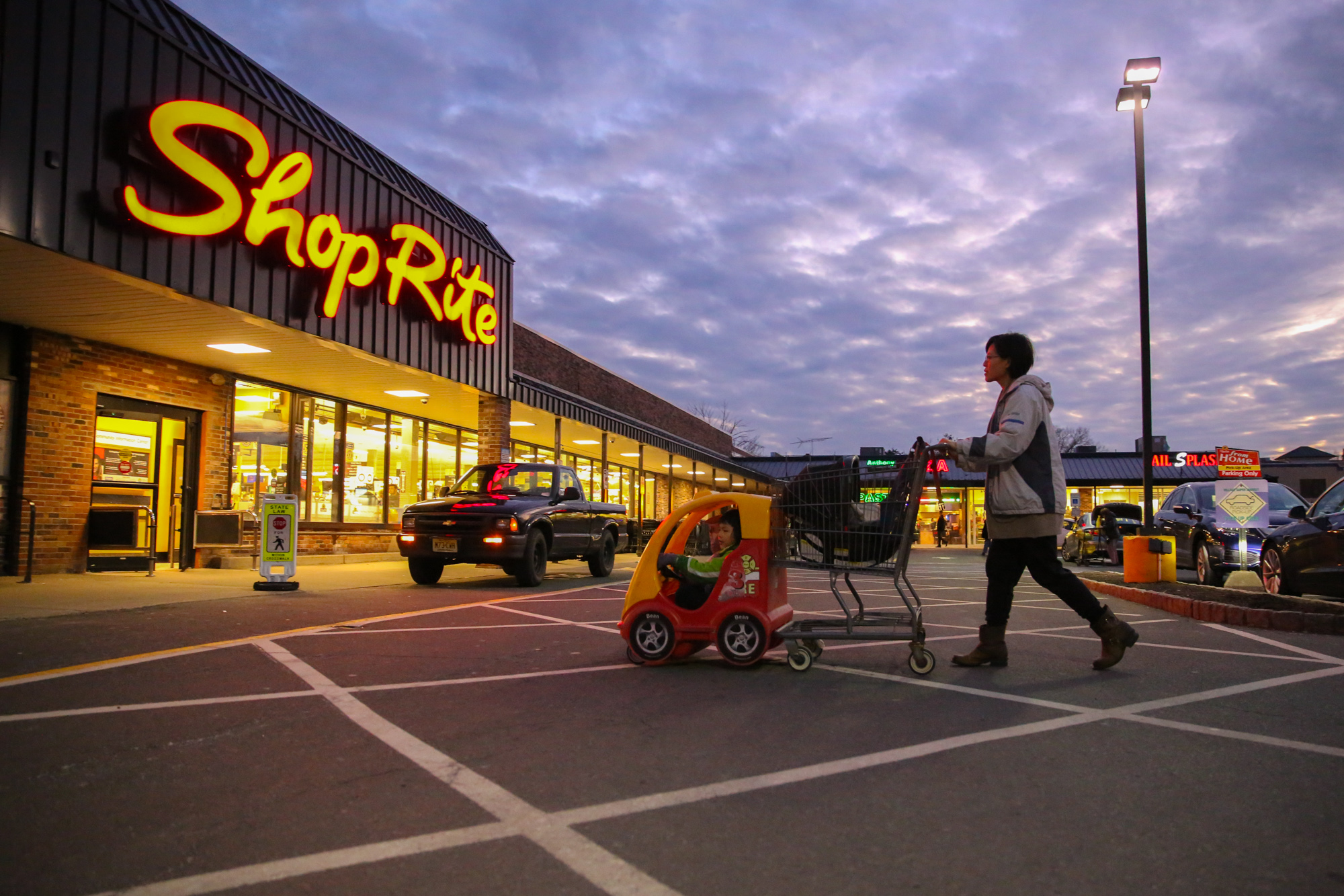 Woman pushes toy car shopping cart into ShopRite grocery store at dusk
